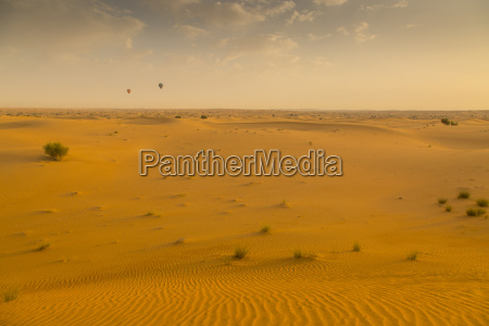 hot air balloons over sand dunes