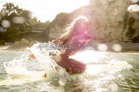 caucasian woman kneeling on surfboard in