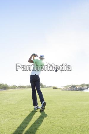 caucasian man teeing off on golf